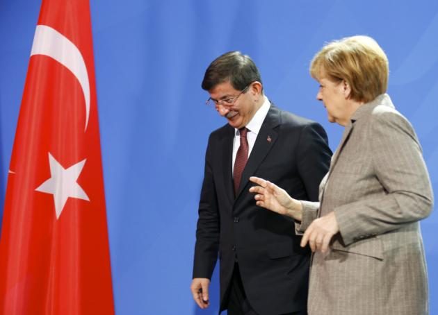 German Chancellor Merkel speaks with Turkish Prime Minister Davutoglu after they addressed the media upon their meeting at the Chancellery in Berlin